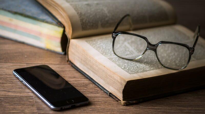 Bog med briller og mobil