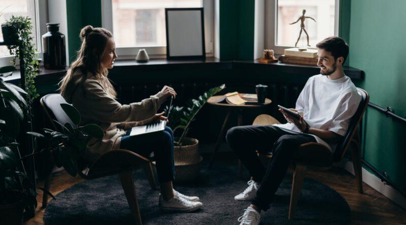 Mand og kvinde som snakker sammen over en computer